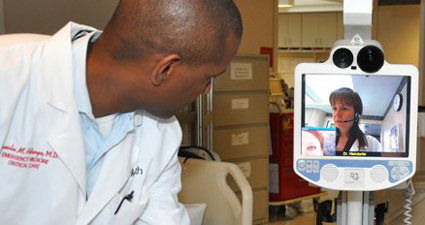 Opeolu Adeoye, MD, demonstrates the telestroke robot at the University of Cincinnati Medical Center. Photo by Cindy Starr / Mayfield Clinic.