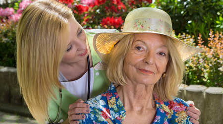 Portrait of Senior Woman with Nurse Outdoors.