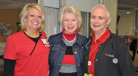 Mary Siereveld, center, prepares to deliver gifts to patients on the neuroscience floor at the UC Medical Center. At left, Lisa Bowman, RN, Nurse Manager on 4 West; at right, Carrie Roark, Medical Assistant at the Gardner Center for Parkinson's Disease and Movement Disorders. Photos by Cindy Starr.