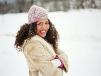 Young woman standing in snow, arms folded, smiling, portrait