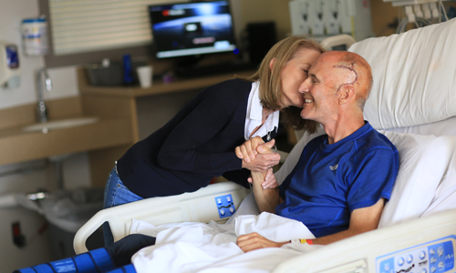 Bob Kehm gets a kiss from his wife, Janice, while recovering in the acuity-adjustable unit after brain surgery at the UC Medical Center.