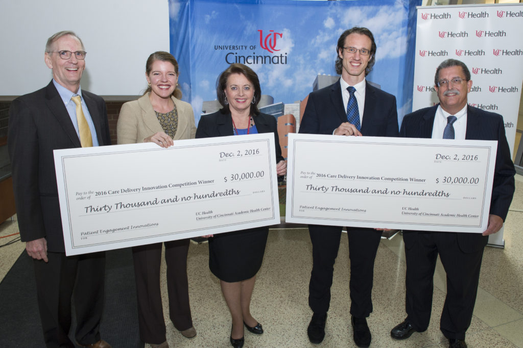 Research award winners holding checks