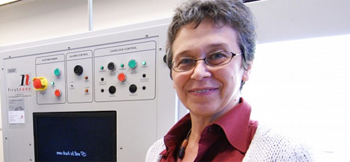 Female researcher stands by lab equipment