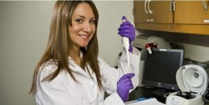 Woman researchers holds test tube, smiling
