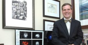 Doctor stands near desk with brain scans on computer.