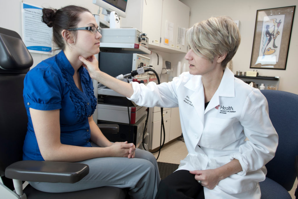Female doctor examines female patient's throat